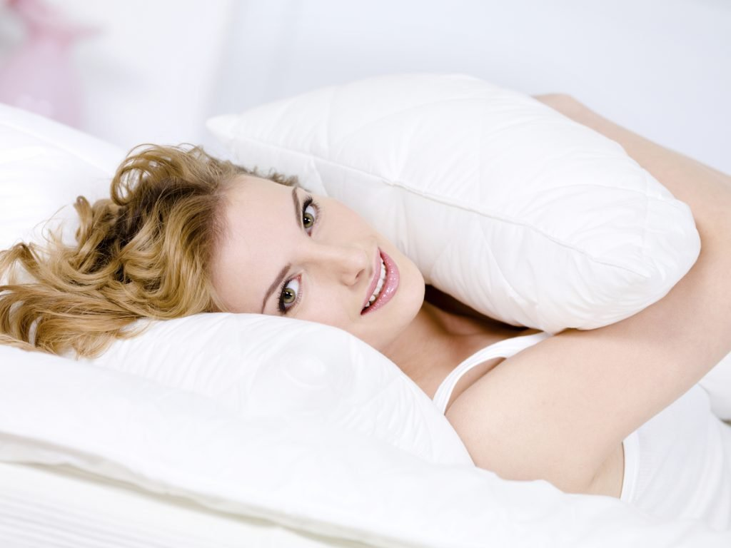 Smiling young woman with pillow relaxing
